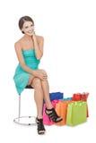 Красивая молодая женщина сидя на стуле рядом с ее покупками Стоковое фото RF