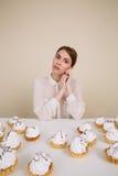 Красивая молодая женщина сидя на таблице с пирожными Стоковые Изображения
