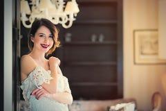 красивая молодая женщина стоя около двери в роскоши Стоковое фото RF