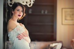 красивая молодая женщина стоя около двери в роскоши Стоковые Фотографии RF