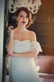 Красивая молодая женщина стоя около двери в светлой роскоши Стоковая Фотография