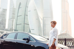 Красивая молодая женщина стоя около черного автомобиля на предпосылке небоскребов Стоковые Фото