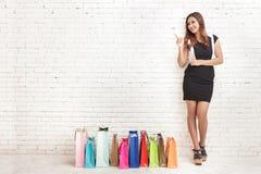 Красивая молодая женщина стоя рядом с хозяйственными сумками пока пункт Стоковое Изображение RF