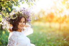 Красивая молодая женщина с венком цветка в саде стоковые фото