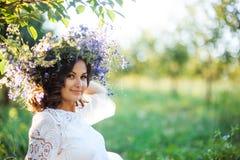 Красивая молодая женщина с венком цветка в саде стоковое фото rf