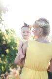 Красивая молодая женщина с девушкой ребенка в поле виноградин стоковая фотография rf