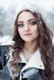 Красивая молодая женщина с длинной прогулкой потехи темных волос в древесинах зимы и играть с снегом в шляпе зимы в черной куртке стоковое изображение rf