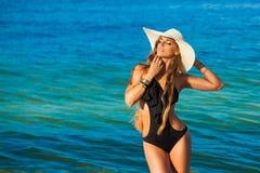 Красивая молодая женщина с длинными волосами в море соломенной шляпы в b стоковые изображения