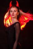 Красивая молодая женщина с красными рожками демона и красными волосами Стоковые Фотографии RF