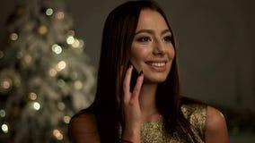 Красивая молодая женщина с профессионалом составляет, говорящ на мобильном телефоне около рождественской елки акции видеоматериалы