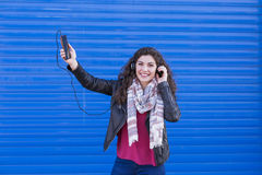Красивая молодая женщина слушая к музыке на ее мобильном телефоне с шлемофоном и имея потеху над голубой предпосылкой вскользь од Стоковое Фото