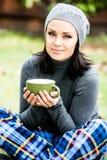 Красивая молодая женщина усмехаясь, выпивая чай стоковые изображения