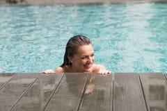 Красивая молодая женщина усмехаясь в бассейне стоковое фото