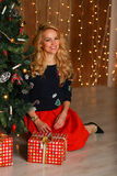 Красивая молодая женщина усмехаясь и сидя на поле около рождественской елки в рождестве украсила интерьер Стоковые Изображения RF