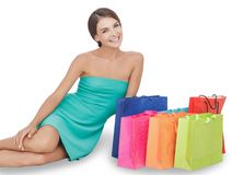 Красивая молодая женщина усмехаясь пока сидящ рядом с ее покупками Стоковые Изображения RF
