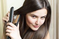 Красивая молодая женщина утюжа ее волосы Стоковые Изображения RF