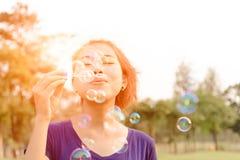 Красивая молодая женщина дуя счастливое пузыря внешнее Стоковое Изображение RF