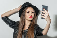 Красивая молодая женщина фотографируя на телефоне Стоковые Изображения