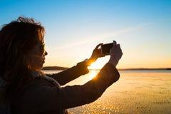 Красивая молодая женщина фотографируя, selfie, на пляже Стоковые Фото