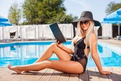 Красивая молодая женщина читает около воды Стоковые Изображения RF