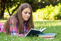 Красивая молодая женщина читая книгу стоковая фотография