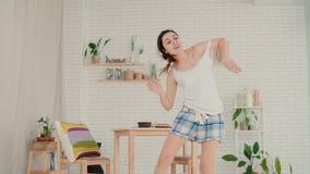 Красивая молодая женщина чувствуя счастливый, скакать и танцевать Девушка брюнет в пижамах имея потеху в утре дома акции видеоматериалы