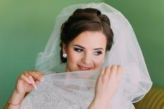 Красивая молодая застенчивая невеста пряча ее сторону за вуалью Стоковое фото RF