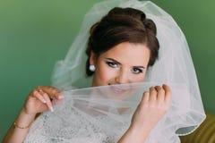 Красивая молодая застенчивая невеста пряча за ее вуалью Стоковая Фотография