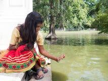 Красивая молодая индийская женщина сидя и играя на озере sid Стоковые Изображения