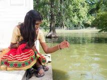 Красивая молодая индийская женщина сидя и играя на озере sid Стоковое фото RF