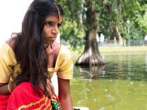 Красивая молодая индийская женщина сидя и играя на озере sid Стоковое Фото