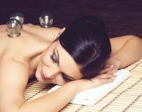 Красивая, молодая и здоровая женщина на бамбуковой циновке в салоне курорта Стоковые Изображения