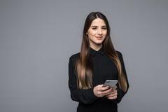 Красивая молодая коммерсантка держа мобильный телефон и смотря камеру пока стоящ против серой предпосылки Стоковые Изображения