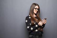 Красивая молодая коммерсантка держа мобильный телефон и смотря камеру пока стоящ против серой предпосылки Стоковые Фотографии RF