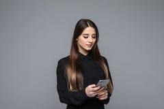 Красивая молодая коммерсантка держа мобильный телефон пока стоящ против серой предпосылки Стоковое Изображение RF