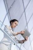 Красивая молодая коммерсантка используя планшет на перилах офиса Стоковые Изображения