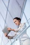 Красивая молодая коммерсантка используя планшет на перилах офиса Стоковая Фотография