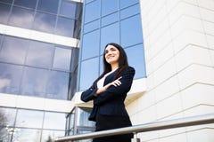 Красивая молодая коммерсантка с пересеченными руками перед небоскребами современного делового центра стоковое изображение