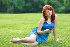 Красивая молодая красная с волосами женщина снаружи в лете слушает к музыке Стоковая Фотография RF