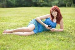 Красивая молодая красная с волосами женщина снаружи в лете слушает к музыке Стоковая Фотография
