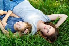 Красивая молодая мать и маленькая дочь лежа на зеленой траве и отдыхать Стоковое Изображение RF