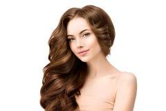 Красивая молодая модельная женщина с сияющими объемистыми волнистыми длинными волосами стоковая фотография