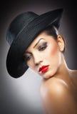 Красивая молодая модель в шляпе на предпосылке в студии Стоковые Изображения RF