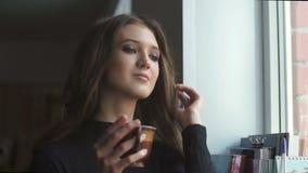 Красивая молодая модель смотрит через окно и выпивает coffe сток-видео