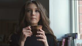 Красивая молодая модель стоя рядом с окном и выпивая coffe видеоматериал