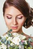 Красивая молодая невеста с флористическим орнаментом в ее волосах красивейше смотрите на ее касающую женщину красивейшая невеста  Стоковая Фотография RF