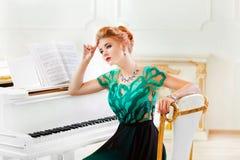 Красивая молодая привлекательная женщина в платье играя белый рояль стоковое фото