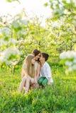 Красивая молодая семья в зацветая саде весны Стоковые Изображения