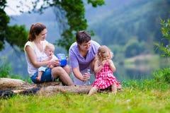 Красивая молодая семья при дети на озере Стоковое Фото