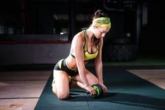Красивая, молодая, сильная девушка практикует в спортзале Он использует имитатор для тренировки подбрюшных мышц, одетый внутри стоковое изображение
